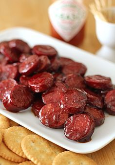 Pomegranate Glazed Sausage: 13oz link of kielbasa, cut into 1/3-inch thick slices (yields about 42 slices). 1/2C pomegranate juice, 1 TBSP ketchup, Tabasco to taste, plus extra for serving. In med skillet, bring pomegranate juice, ketchup, and dash of Tabasco to boil. Boil 2-3 min or until becomes syrupy. Add slices to sauce and cook over high heat, turning slices occasionally, until mixture reduces almost completely and coats sausage,(2-3 min). Serve w/ toothpicks or ritz