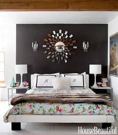 Things I love about this bedroom: the dark slate (or black) wall, floral bedding that is somehow NOT overly feminine, the shaggy white pillow and fur throw, and especially the modular nighstands and modern white lamps with stacks of books and little vases with pink flowers