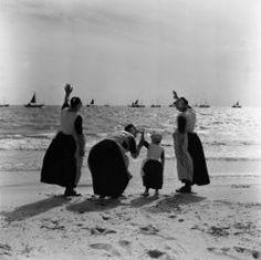 Urk, vrouwen en kind in klederdracht zwaaien naar schepen op zee Collectie Stadsarchief Amsterdam #Urk