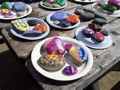 Place rocks/stones over campfire to get hot. Then put them on picnic table and have kids color them with crayons. The crayons melt onto the stone making it look like paint! We did this on our girl scout camp outs.