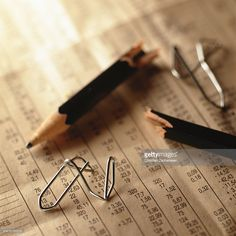 Broken pencil and twisted paper clips on top of financial numbers.