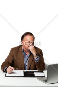 businessman looking at laptop with hand on chin. - Mature businessman looking at laptop with hand on chin while at work, Model: Dan Sanderson