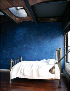 starry night dark navy wall treatment with skylight and exposed beams makes for a dreamy bedroom