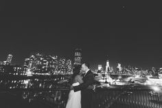 Bride and groom take a photo with the NYC skyline from the Maritime Parc in Jersey City, NJ. Captured by NYC wedding photographer Ben Lau.