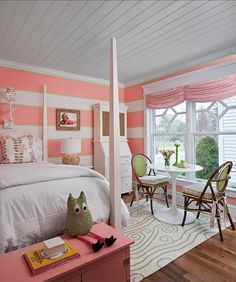 Sweet girl's room boasts plank ceiling over white and coral pink striped walls framing white 4 poster bed dressed in pale gray bedding and pink and green pillows beside white bedside table topped with round driftwood lamp and white secretary desk alongside a pink trunk placed at the foot of the bed. A Saarinen Table paired with woven chairs atop white and green rug is placed in front of windows dressed in pink ruched shades with pink pom pom fringe.