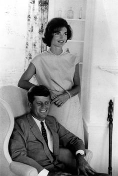 john f. kennedy sitting down while his wife is standing next to him in their summer home in hyannis port.