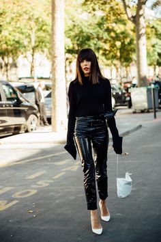 Black patent vinyl pants hit above the ankle and are paired with a black sweater with extra long sleeves, white pumps and a white bag. Street Style 2017, Street Style Trends, Grey Fashion, Minimal Fashion, Autumn Fashion, Womens Fashion, Fashion Trends, Vinyl Pants, Vinyl Trousers
