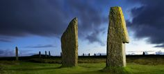 Picture of the Ring of Brodgar, a henge monument with a stone circle in Scotland, the sky is a dark blue and the grass is very green