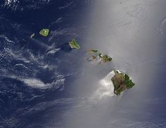 A true-color satellite view of Hawaii shows that most of the vegetation on the islands grows on the northeast sides which face the wind. The silver glow around the southwest of the islands is the result of calmer waters.[60]
