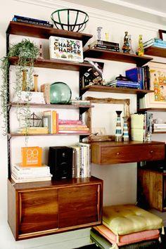 étagère en bois foncé , bibliothèque murale, livres, mur blanc, plante verte