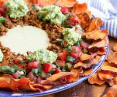 Paleo nachos with sweet potato chips, spicy beef, salsa and dairy-free cheese sauce