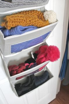 organize gloves and hats with a pocket organizer with clear windows that hangs over the door