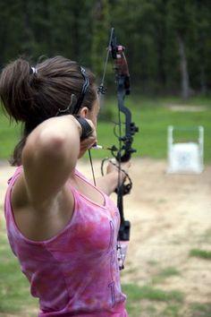 Busty girl shooting bow