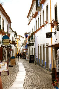 Why you need to visit Obidos in Portugal - via AnnieAnywhere 16.02.2015 | The ultimate reason to visit Óbidos is just because it's adorable. This small village is build within castle walls, and going there is like a time-travel in middle ages. Photo: Obidos Main Street