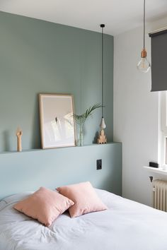 Pastel green bedroom with light pink pillows and wooden interior decor. We love the simple and Scandinavian inspired look as well as the pendant lights.