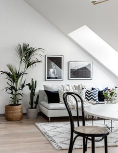 Sloped ceiling in living room with large window, grey couch, art above couch and plants