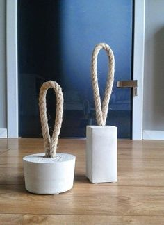 Do-it-Yourself Concrete Door Stoppers — Home Made Makeovers Aligol of Home Made Makeovers crafted these two big-in-size, big-on-style door stops just by mixing up some basic home store concrete mix, using a milk carton or plastic tub as a mold. The concrete just needs to be fitted with a coupler and a loop of rope before setting for a few days.