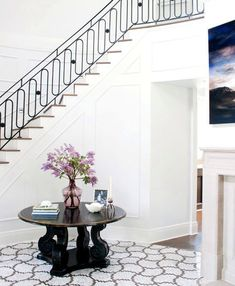 foyer entry hall two story stairs staircase round entry table marble mosaic floor