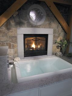 Infinity bath tub...love the beams and stone...fireplace