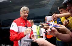 Fan favourite: Arsene Wenger signing autographs for fans upon arrival...