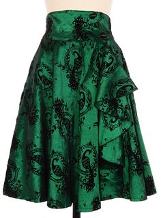 """This skirt will be the crowning jewel of your wardrobe! In shimmery emerald green taffeta with the prettiest black velveteen peacock cameos print on top, and a wide banded high waist, the flattering fit and flared cut of this knee length skirt is pure pin-up perfection! Also available as a dress. Fit Runs Slightly Small. Length: 26"""". 65% Poly, 30% Nylon, 5% Spandex Dry Clean Only. Back Zipper Closure. photo 1/3"""