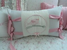 Almofada com laços nas laterais da almofada e aplicação de passarinho no centro da almofada. <br>Mede 32 x 47 cm