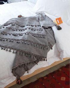 Designer Randi Brookman Harris sewed tassels on to herringbone fabric to create an elegant tasseled blanket inspired by 17th century state beds.