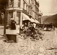 Dette bildet viser vedsaging på Torgallmenningen i Bergen. Det er veldig hverdagslig i sitt utrykk, men unikt på grunn av vi ikke kjenner til andre slike bilder fra sentrum. Det var stor vedfrakt inn til vågen hvor veden ble solgt fra båt. Om veden sages opp for salg, eller om en kunde har kjøpt et favn og leid inn sagehjelp kan vi kun spekulere i. Bildet er fra rundt 1900, fotografen er ukjent. Billedsamlingen - UiB