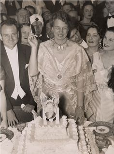 Eleanor Roosevelt holding a knife preparing to cut FDR's birthday cake at one of the Birthday Balls. 1930s.