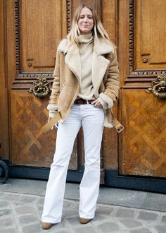 Loose fitting camel turtleneck sweater layered under a shearling jacket with white flare jeans