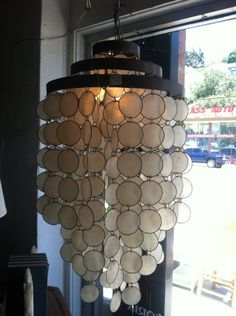 This unique 1960s capiz shell chandelier has three bands of brass on the top.