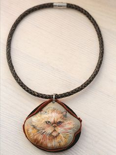 Natural stone necklace ornamented with a hand-painted miniature of a persian cat.  The 6 by 7 cm stone pendant has a layer of felt beneath that allows