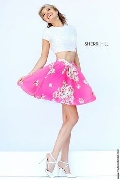 Pearly beads grant a dainty appeal to the two-piece ensemble of Sherri Hill 32251 short dress, dominating the crop top sporting a circular cutout back. The jewel neckline sits in between a pair of short sleeves, capping the beaded bodice that halts at the midriff. At the natural waist, the floral print skirt takes off and flourishes into the cocktail length with a fluttering hemline. Available in Ivory-Blue Print and Ivory-Pink Print as shown.