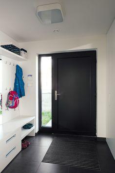 Vstupní dveře mají stejnou barvu jako hliníkové rámy oken. Jejich součástí je i boční světlík, který zajišťuje denní světlo v prostoru zádveří.