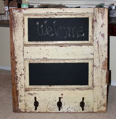 REPURPOSED door cut in half. Sections are painted with chalkboard paint and hooks are screwed in at the bottom. I think the old hinge makes it a great conversation piece. It has a story to tell.