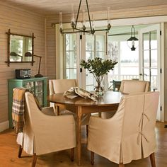 In the natural-hued dining room, French doors open to a screened porch with stunning water views. Sophisticated chair covers add to the simple elegance of the space.