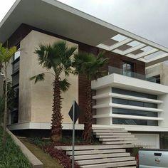 Fachada com elementos vazados no beiral, escada frontal em dois lances, vidro, madeira, pintura branca e pedra natural. #fachadasminimalistasdepartamentos