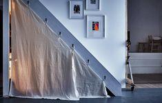 Quarto de brincar de criança, debaixo de um vão de escadas, com um tecido pendurado como entrada, algumas almofadas, uma prateleira e uma caixa cheia de brinquedos