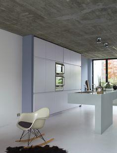 Stijlvol leeg. Zo komen de materialen in deze keuken echt tot hun recht. Het plafond in ruw beton boven een kookeiland in ondoorgrondelijk 'cement'. De kastenwand in 'sereen' naast een muur in een mysterieuze 'waas'. Alle aandacht voor stijlvolle kleurcombinaties en design. (collectie: Eenvoud Siert)