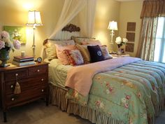 This bedroom achieves cottage style by mixing floral prints and sheer draperies with simple, antique furnishings. A color palette of greens, creams and pinks lightens the space, while soft lighting adds a romantic touch. Design by 11044991.