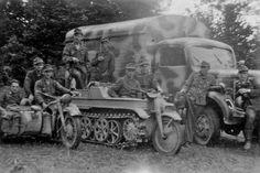 Soldados posando junto a varios vehículos, en el centro un Sd.Kfz 2 - Kleines Kettenkraftrad.