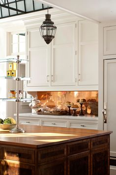 Bright touches--Other glitzy features that add sparkle to a traditional kitchen include antiqued mirrors and polished copper on backsplashes, cabinet door and refrigerator fronts, and even mirrored toe kicks (they reflect the floor).