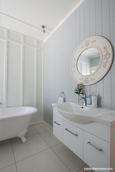 The stunning bathroom has a board and batten feature wall, painted in Resene Quarter Cararra. Resene Hermitage, on the tongue and groove walls, completes the blissful colour combo. Project by David Wraight Cottages, photo by Juliet Nicholas. http://www.habitatbyresene.co.nz/kirsty-and-david-set-tone-old-new