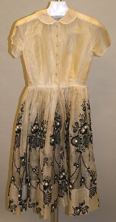 White cotton cocktail dress with black embroidery (worn with cotton petticoat), by Norman Norell for Traina-Norell, American, 1952-57.