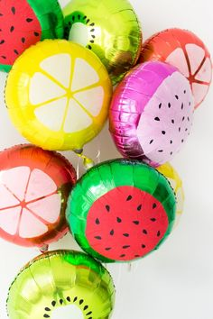 DIY Fruit Slice Balloons  Buy a mylar balloon and stick to it the red watermelon center or lemon slices etc.