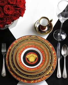 VERSACE:  A combo of red, white and gold dinnerware, flatware,  and glasses would look great with black and white linen and red roses.