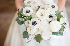 classically beautiful all white bridal bouquet of white garden roses, white ranunculus, button camomile, white majolik spray roses, white anemone with navy center, dusty miller, eucalyptus and bay leaf.
