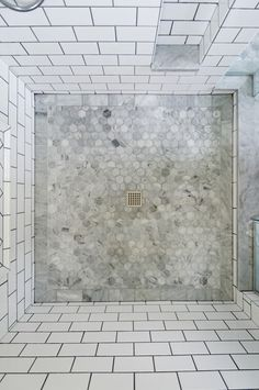 The shower enclosure features a base of hexagon patterned tile, bordered by marble subway tiles.