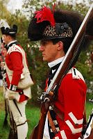 The Coats of the 16th are red, faced with blue wool. The buttons, in pairs, are set on length- way along the arms. Lapels, cuffs and collar are of blue wool. The lace of the the light dragoons is white wool worsted. (In the infantry this is relegated to Serjeants only.) Waistcoats, breeches and coat lining are white. The helmet is made of leather with a bearskin crest with a painted leopard turban. Gaiters are of brown wool with a hard leather top to protect the knees.