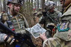 Air Force 1st Lt. David Murphy and Airmen participating in Exercise Scorpion Lens 15 analyze a map for directions at North Auxiliary Airfield, SC. Exercise Scorpion Lens 2015 is an annual exercise designed to validate the ability of Air Force Combat Camera Airmen to survive, operate and provide directed imagery capability in an austere environment including in the presence of chemical, biological, radiological and nuclear contamination.